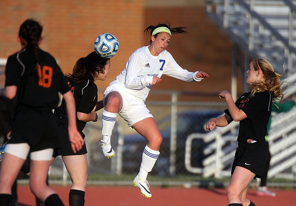 Jeff Krage – For Shaw Media<br /> St. Charles East's Shannon Gatehouse heads the ball away from St. Charles North's Ashlyn Walter during Tuesday's game.<br /> St. Charles 4/22/14