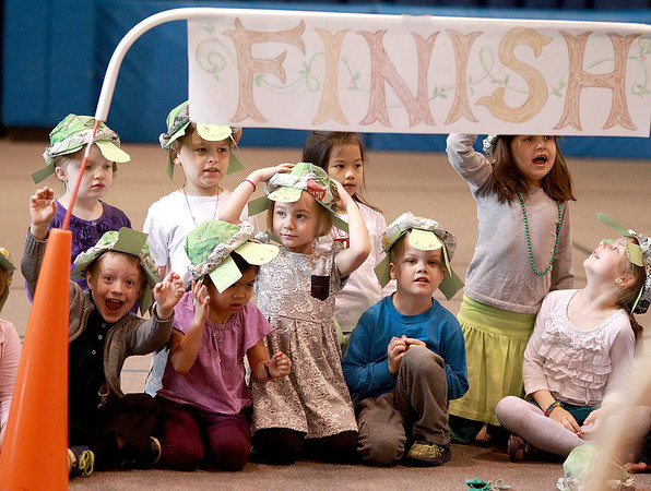 Students at Faith Christian School in Geneva wear furtle hats they made as they watch a race between a rabbit and a tortoise Thursday as part of their lesson on Aesop's fable, The Tortoise and the Hare.