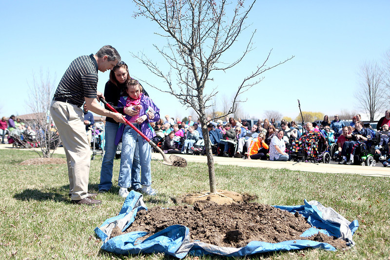 Shelley B., a resident  at Marklund at Mill Creek in Geneva, shovels dirt during a tree planting with the help of Marklund President and CEO Gil Fonger and developmental instructor Melissa Majeski during the facility's Arbor Day celebration Friday.