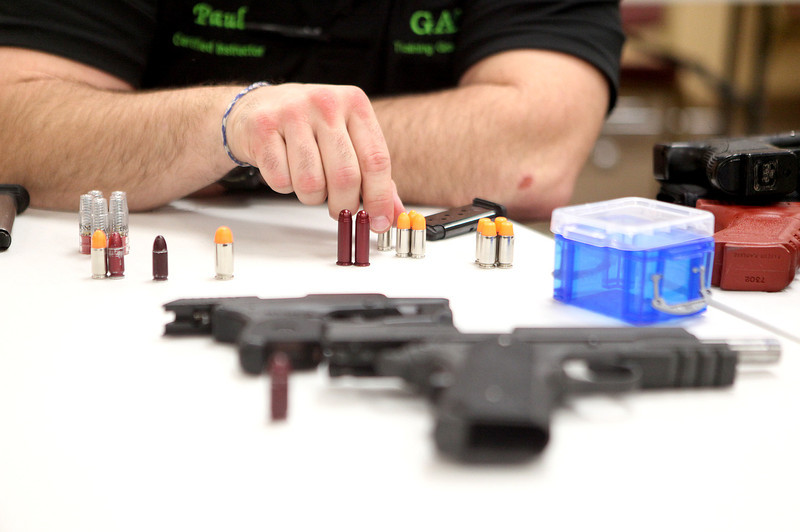 Paul Warren, a sergeant with the Kane County Sheriff's Office, shows some of the different types of handguns and bullets during a conceal carry class at GAT Guns in East Dundee.