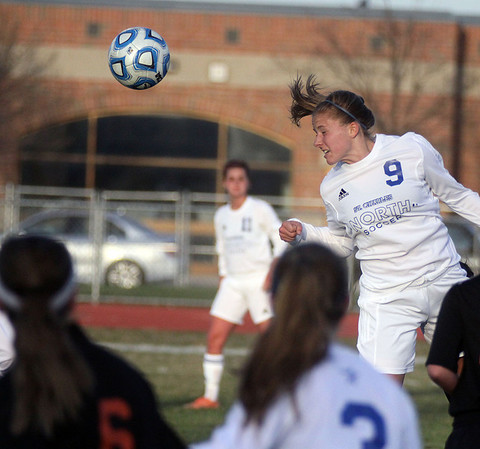 Jeff Krage – For Shaw Media<br /> St. Charles North's Alyssa Brandt heads the ball out of the box during Tuesday's game against visiting St. Charles East.<br /> St. Charles 4/22/14