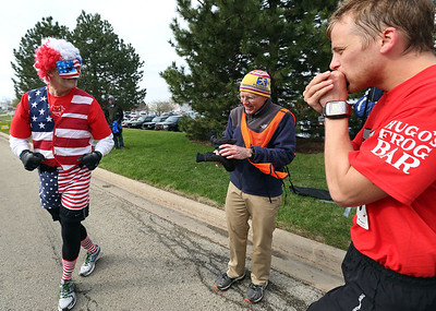 Dressed as Mr. America Mike Splitt, left, from Crystal Lake, talks with race official Bon Wlash, center, from Crystal Lake, as Curtis Weisenburger, from McHenry, keeps warm at the start of the Human Race in McHenry Sunday, April 27, 2014 in McHenry. Weisenburger won the 5K run with a time of 16:08.  Each race participant designates what charity organization will receive the proceeds of their race fee, Splitt was running for the charity Options & Advocacy. The race supports over 50 charities serving McHenry County IL.  John Konstantaras photo for the Northwest Herald