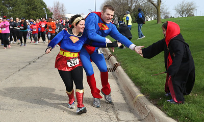 Abbie Farmer, left, 7, greets her parents Jeff and Jennie at the start of the Human Race Sunday, April 27, 2014 in McHenry. The race is a unique 5K run and walk that supports over 50 charities serving McHenry County IL. Each race participant designates what organization will receive the proceeds of their race fee. The Farmers were running for the Turning Point.  John Konstantaras photo for the Northwest Herald