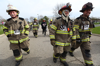 Members of the Spring Grove Fire Protection District (L-R) Asst, Chief Bob Stevens, Captain Dean Jordan and Captain Kevin Young wear their full fire gear as they walk in the Human Race Sunday, April 27, 2014. The race is a unique 5K that supports over 50 charities serving McHenry County IL. Each race participant designates what organization will receive the proceeds of their race fee. The firefighters were walking for Explorer Post 1800.  John Konstantaras photo for the Northwest Herald