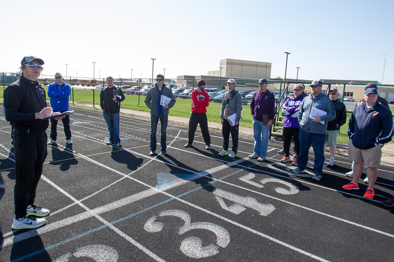 Kaneland Track and Field Coach and Head Official Eric Baron (Left) talks to team coaches and gives out assignments in a quick meeting prior to the start of The Peterson Prep Track Meet at Kaneland High School in Maple Park, IL on Saturday, April 26, 2014 (Sean King for Shaw Media)
