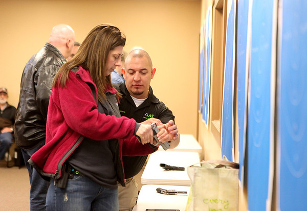 Ever Saenz of the Kane County Sheriff Department instructs Susan Schroeder during a conceal and carry class at Gat Guns in West Dundee.