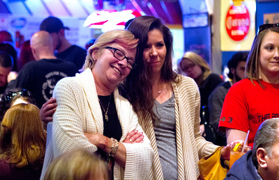 Mike Greene - For Shaw Media Trish Neal, left, is embraced by Sarah Alich, of Crystal Lake, while listening to Mike Neal speak during the third annual Walk for The Brighter Side fundraiser Saturday, April 11, 2015 at Nero's Pizza & Pub in Algonquin. The event featured a photobooth, 50/50 raffle, a raffle for over 60 donations, speakers and a buffet donated by Nero's Pizza & Pub.