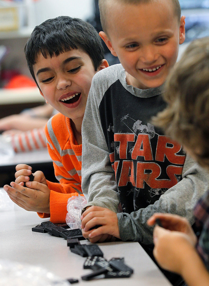 Matthew Apgar - mapgar@shawmedia.com Husmann Elementary School students (from left:) Jack Frailey, Jimmy Czeslawski, and Asher Johnson break out in laughter after a row of dominoes falls they way they planned it to during STEM (Science Technology Engineering Mathematics) class on Monday, April 20, 2015 at Husmann Elementary in Crystal Lake. The students were learning about forces needed to push and pull objects.