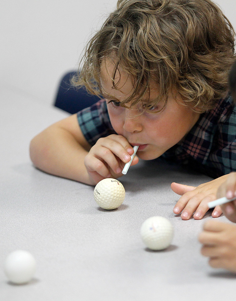 Matthew Apgar - mapgar@shawmedia.com Husmann Elementary School student Asher Johnson uses a straw to make a pingpong ball move during STEM (Science Technology Engineering Mathematics) class on Monday, April 20, 2015 at Husmann Elementary in Crystal Lake. The students were learning about forces needed to push and pull objects.