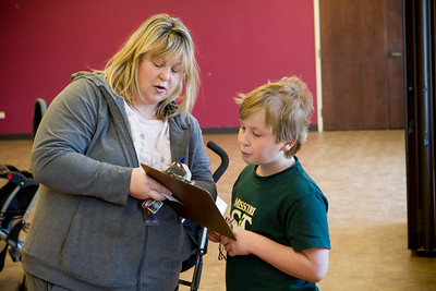 Mike Greene - For Shaw Media Jennifer Wiley, of Lake in the Hills, walks through a purchase form with her son Thomas, 9, during the Second Annual Wheels and Deals Sale Saturday, April 16, 2016 at Village Hall in Lake In The Hills. The program allows sellers to determine the selling price, with the city co-oping the sale, and sellers receive 80% of the price on items sold.