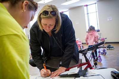 Mike Greene - For Shaw Media Dani Flynn, of Crystal Lake, purchases a bike for her son during the Second Annual Wheels and Deals Sale Saturday, April 16, 2016 at Village Hall in Lake In The Hills. The program allows sellers to determine the selling price, with the city co-oping the sale, and sellers receive 80% of the price on items sold.