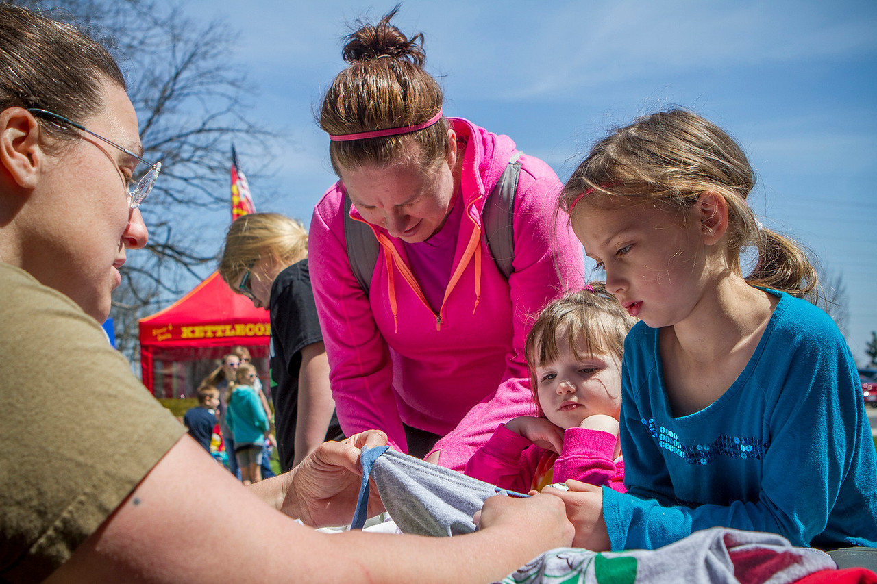 Mike Greene - For Shaw Media Abigail Lobo, right, 6 of Woodstock, makes a reusable bag out of a shirt with her sister Katie, center, 3, and mother Janet during Earth Day Celebration 2016 Saturday, April 23, 2016 at Prairieview Education Center in Crystal Lake. The event included guided nature hikes, games and crafts, puppet Shows, over 20 environmental exhibitors, as well as food & beverage vendors.