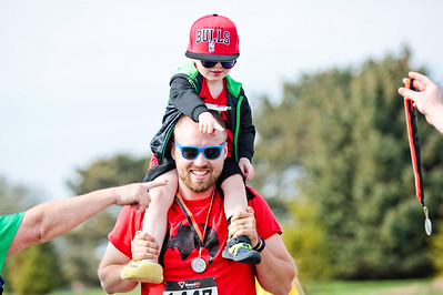 Michelle LaVigne/ For Shaw Media While getting ride from his dad Drew Kunde of Woodstock, two-year-old Dylan is handed a medal after completing the McHenry County Human Race held at McHenry County College on Sunday April 24, 2016.