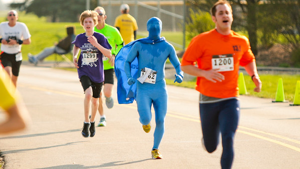 Michelle LaVigne/ For Shaw Media Wearing all blue and a cape, Greg Bielak of Lake Zurich heads to the finish line at the McHenry County Human Race held at McHenry County College on Sunday April 24, 2016.