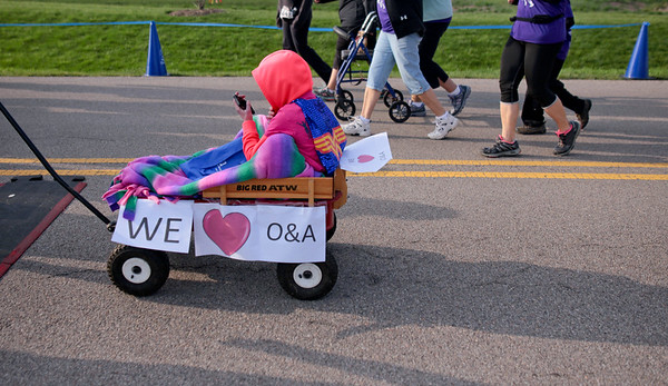 Michelle LaVigne/ For Shaw Media Ten-year-old Katie Thomas of Bull Valley is able to hitch arride from her dad during the McHenry County Human Race held at McHenry County College on Sunday April 24, 2016.
