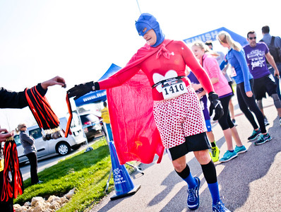 "Michelle LaVigne/ For Shaw Media Dan Keppel of Spring Grove, or ""Dr. Love,"" takes his medal for completing the McHenry County Human Race held at McHenry County College on Sunday April 24, 2016. Keppel was running in support of Habitat for Humanity. He chose his outfit and superhero character based around the heart decorated boxers he already owned. ""I had to find something to go with my shorts."""