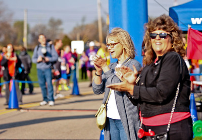 Michelle LaVigne/ For Shaw Media While waiting for their children to cross the finish line, Marcy Pickos of Woodstock (furthest,) and Janet Rosenbach of Huntley, cheer on the runners in the McHenry County Human Race held at McHenry County College on Sunday April 24, 2016.
