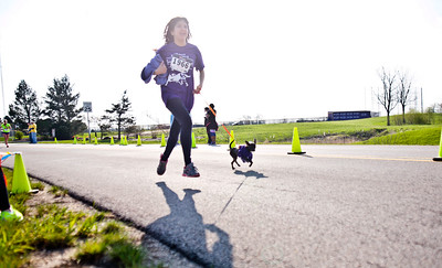 "Michelle LaVigne/ For Shaw Media Fourteen-year-old Daniela Bandala of McHenry and her running companion Midnight, near the finish line McHenry County Human Race held at McHenry County College on Sunday April 24, 2016. Bandala and Midnight were running for Garden Quarter Neighborhood Resource Center, a center of education and support for children. Bandala said Midnight was a help during the whole race.  ""He makes me run."""
