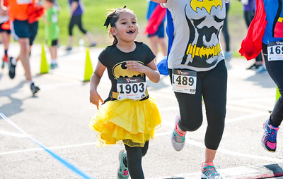 Michelle LaVigne/ For Shaw Media COVER Dressed as batgirl, six-year-old Aliza Roman of McHenry crosses the finish line of the McHenry County Human Race held at McHenry County College on Sunday April 24, 2016. Roman was running to support the Court Appointed Special Advocates (CASA) of McHenry County which helps give foster children who are victims of abuse a voice in court.