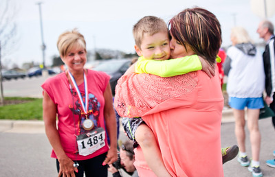 Michelle LaVigne/ For Shaw Media Four-year-old Brody Losch of Crystal Lake receives a congratulatory kiss from his mother Jenni after crossing the finish line during the toddler division of the McHenry County Human Race held at McHenry County College on Sunday April 24, 2016,