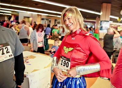 Michelle LaVigne/ For Shaw Media Robin Doeden of Lake in the Hills attaches her bib before the start of the McHenry County Human Race, held at McHenry County College on Sunday April 24, 2016. Participants chose which charity they want their race fee to benefit and Doeden was running to support the McHenry County Community Foundation charity.
