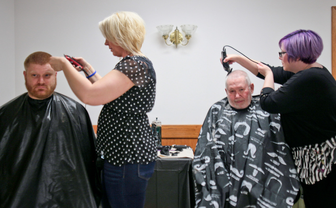Michelle LaVigne/ For Shaw Media Left to right, Navy veteran Mark Handeland of Woodstock receives a trim from Erica Zarnstorff of Woodstock while Army veteran Donald Stage of Woodstock receives a buzz from Jessica Tifft of Belvidere during the Veteran Stand Down Resource Fair held at the McHenry VFW on Thursday, April 28 2016. The event was hosted by the McHenry County Veterans Assistance Commission.
