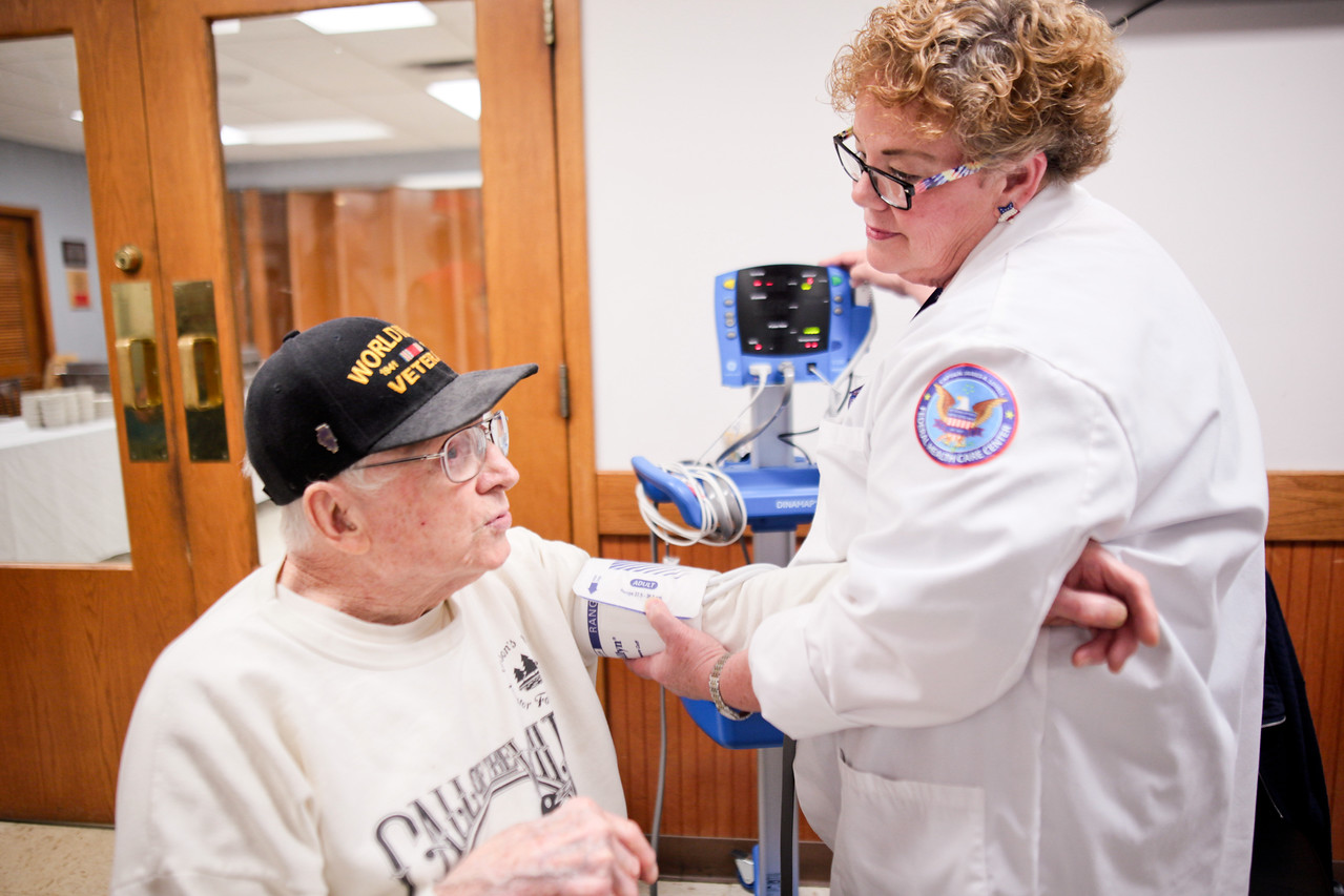"""Michelle LaVigne/ For Shaw Media WWII and Korean war veteran Howard Lexow of McHenry receives a free blood pressure screening from LPN Missy Robel of Ringwood while attending the Veteran Stand Down Resource Fair held at the McHenry VFW on Thursday, April 28 2016. Robel said she valued working with veterans like Lexow. """"It's not a job, it's an honor."""""""
