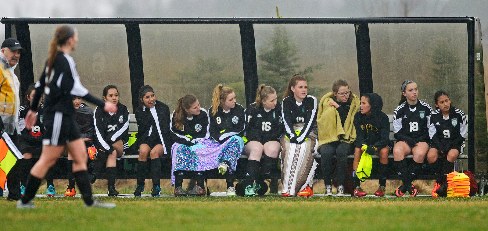 The Woodstock North team attempts to stay warm and dry on the bench Monday April 3, 2017, during a game at Hampshire High School. Woodstock North won 3-2.