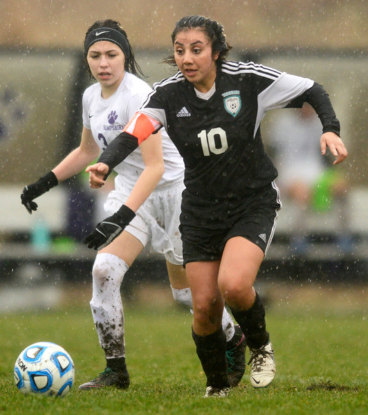 Hampshire freshman Alessa Carranza tails behind Woodstock North Daniela Miranda during a game at Hampshire High School on Monday April 3, 2017. Woodstock North won 3-2.