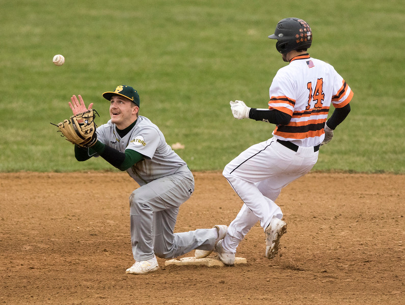 Sarah Nader - snader@shawmedia.com Crystal Lake South's Scott Skwarek (left) waits for the ball while McHenry's Brendon LoPresti safely runs to second base during the second inning of Tuesday's game in McHenry April 4, 2017.