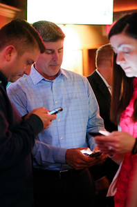 Cary Trustee Jim Cosler, center, checks results for his mayoral race with Chris Covelli, left, and Kim Covelli at Tracks Bar and Grill on Tuesday, April 4, 2017 in Cary. Cosler was in a close race with Mark Kownick. John Konstantaras photo for the Northwest Herald