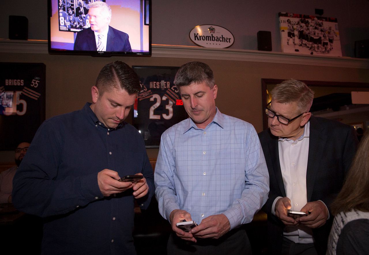 Cary Trustee Jim Cosler checks results for his mayoral race with Chris Corelli (left) and Mike Rein at Tracks Bar and Grill on Tuesday, April 4, 2017 in Cary. Cosler was in a close race with Mark Kownick. John Konstantaras photo for the Northwest Herald