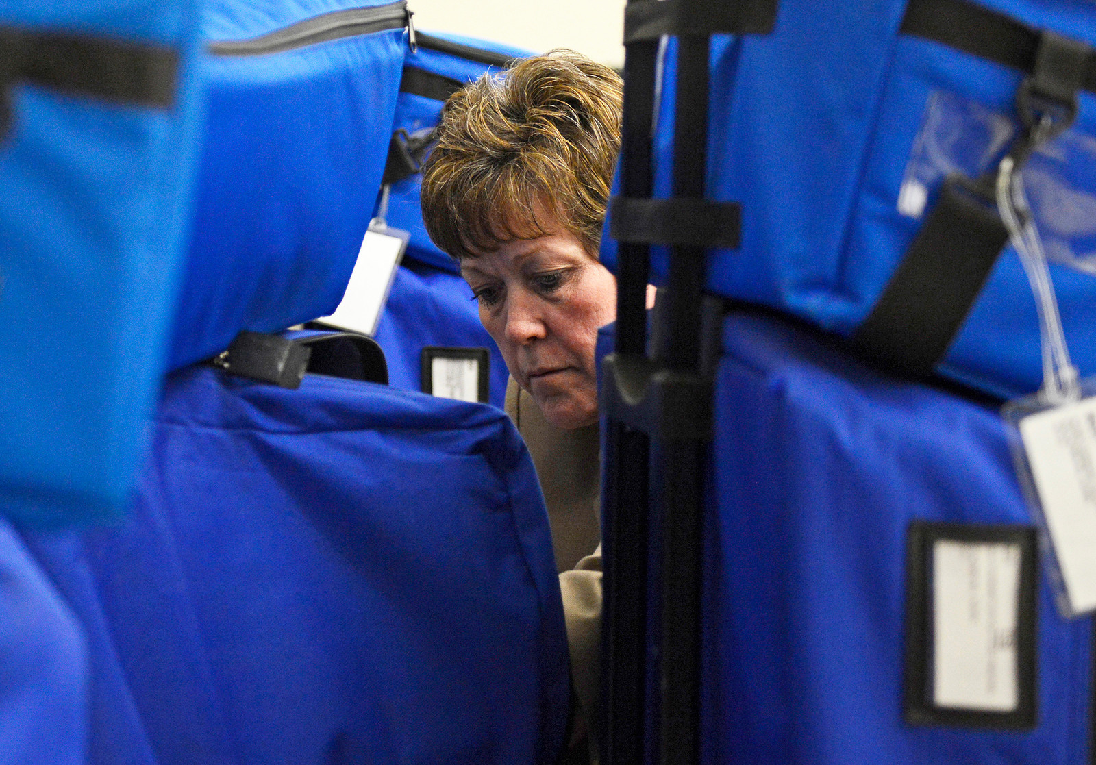 Kayla Wolf - For Shaw Media McHenry County Clerk Mary McClellan removes the memory cards from each electronic voting machine April 4, 2017, at the McHenry County Administration building in Woodstock. After removing the cards McClellan took them to be uploaded directly to the counting machine.