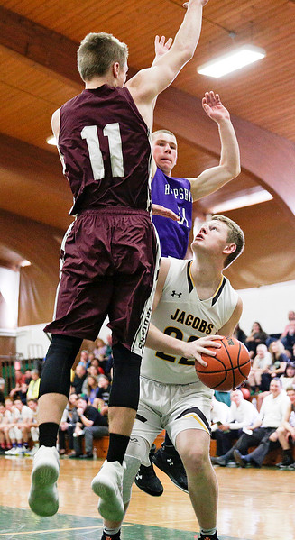 Mason Materna from Jacobs looks to the basket as Mike Volkening (11) from Marengo and Billy Dumoulin go high to defend during the first half of the Boys all-star basketball game at Alden-Hebron High School on Sunday, April 9, 2017 in Hebron, Ill. The away team won the game 87-86.  John Konstantaras photo for the Northwest Herald