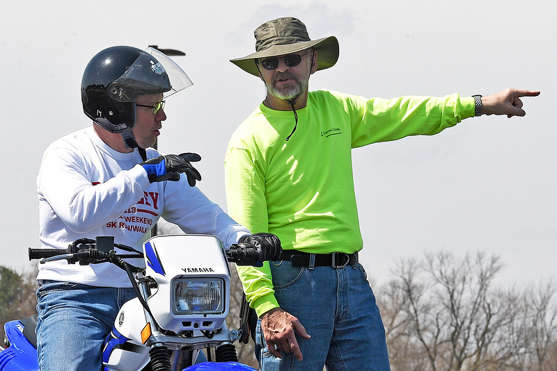 Rider Coach Mark Wilson explains a riding exercise to Jerry Niederman Saturday, April 15, 2017, during a motorcycle course held at McHenry County College.