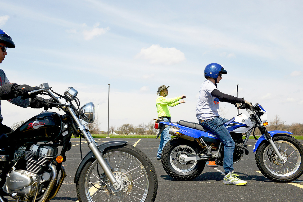 Rider Coach Mark Wilson instructs students how to start their motorcycles during a course Saturday, April 15, 2017, held at McHenry County College. Wilson instructs motorcycle courses for Harper College and travels around Lake, Cook, McHenry and other surrounding counties teaching riding classes throughout the summer.