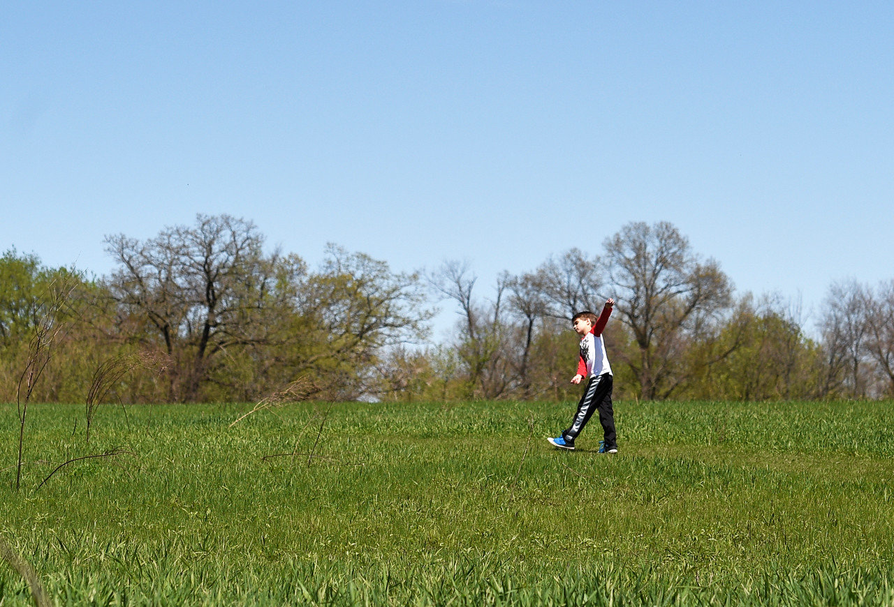 Kayla Wolf for Shaw Media- Will Calhoun runs around grass paths at Prairieview Education Center on Saturday, April 22, 2017 during an Earth Day celebration. The event offered live musical performances, guided nature hikes, games and crafts, puppet shows, environmental exhibits and food vendors.