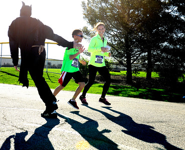 Kayla Wolf for Shaw Media- Batman Lee Stiemke high-fives McHenry County Human Race participants Brian Bennet and Piper Bennett Sunday, April 23, 2017, as the run to the finish line. The race has raised over $222,000 in the last three years.