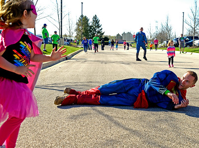 Kayla Wolf for Shaw Media- Charlotte Stiemke (left) laughs Sunday, April 23, 2017, as Bryan Henning pretends to fall as she beats him to the finish line at the McHenry County Human Race. There was a toddler race that happened during the large 5K.