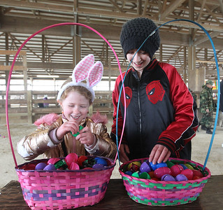 Candace H. Johnson-For Shaw Media Bella VanHorn, 7, of Round Lake and her sister, Adrianna, 10, look through the plastic eggs they collected to look for a prize slip during the Re/Max Center's Easter Egg Hunt at the Lake County Fairgrounds in Grayslake.(3/31/18)