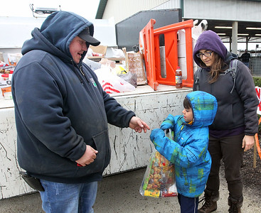 Candace H. Johnson-For Shaw Media Aubrey Wuchter, of Johnsburg, with Warren Township's grounds and maintenance, takes a bag of donated food from George Garcimartin, 6, of Gurnee and his mother, Christina, for the Warren Township Food Pantry during the Re/Max Center's Easter Egg Hunt at the Lake County Fairgrounds in Grayslake.(3/31/18)