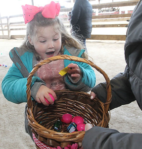 Candace H. Johnson-For Shaw Media Quinn Sandine, 6, of Gurnee reacts to finding a prize slip in one of the plastic eggs she picked up as her mother, Nicole, holds her basket during the Re/Max Center's Easter Egg Hunt at the Lake County Fairgrounds in Grayslake.(3/31/18)