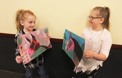Candace H. Johnson-For Shaw Media Eden Hamelberg, 8, of Antioch and her sister, Mya, 10, show each other the horse drawings colored with pastels they made during the Horses Art Camp at the Hunt Club Community Center in Gurnee.