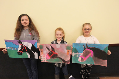 Candace H. Johnson-For Shaw Media Landry Lies, 10, of Gurnee stands next to Eden Hamelberg, 8, of Antioch and her sister, Mya, 10, as they show off their pastel drawings of a horse they made during the Horses Art Camp at the Hunt Club Community Center in Gurnee.