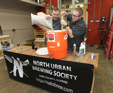 Candace H. Johnson-For Shaw Media Dan Berger, of Libertyville and Matt King, of Mundelein, members of the North Urban Brewing Society, put grain into hot water as they make a mash while brewing beer at Perfect Brewing Supply in Libertyville.(4/3/18)