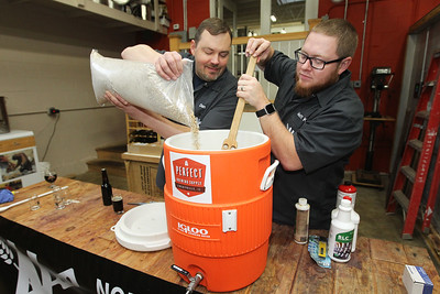 Candace H. Johnson-For Shaw Media Dan Berger, of Libertyville and Matt King, of Mundelein, members of the North Urban Brewing Society (NUBS), put grains into hot water to make a mash as they brew beer at Perfect Brewing Supply in Libertyville.(4/3/18)