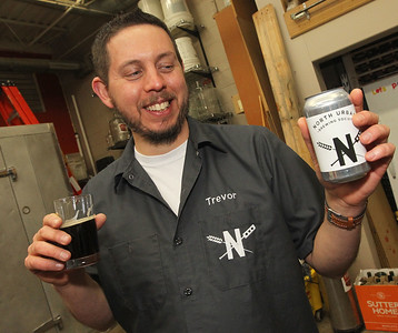 Candace H. Johnson-For Shaw Media Trevor Patric, of Volo, president, holds up a North Urban Brewing Society beer can that is used for beer made by the club and shared at craft beer festivals at Perfect Brewing Supply in Libertyville.(4/3/18)