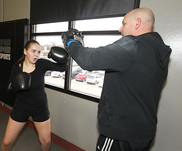 Candace H. Johnson-For Shaw Media Bella Crothers, 16, of Grayslake works with Coach Larry Lentz, of Round Lake Park, owner, on hand mitt training as she prepares to fight in the Chicago Golden Gloves Finals at the Conquer Fight Club located inside the Libertyville Sports Complex.(4/5/18)