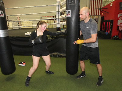 Candace H. Johnson-For Shaw Media Bella Crothers, 16, of Grayslake works on her power punches as Albert Ciszewski, of Lake Villa holds the punching bag while she trains to fight in the Chicago Golden Gloves Finals at the Conquer Fight Club located inside the Libertyville Sports Complex.(4/5/18)