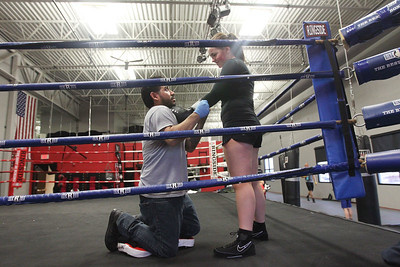 Candace H. Johnson-For Shaw Media Coach Angel Lopez, of Waukegan helps Bella Crothers, 16, of Grayslake put on her boxing gloves while training for the Chicago Golden Gloves Finals at the Conquer Fight Club located inside the Libertyville Sports Complex.(4/5/18)